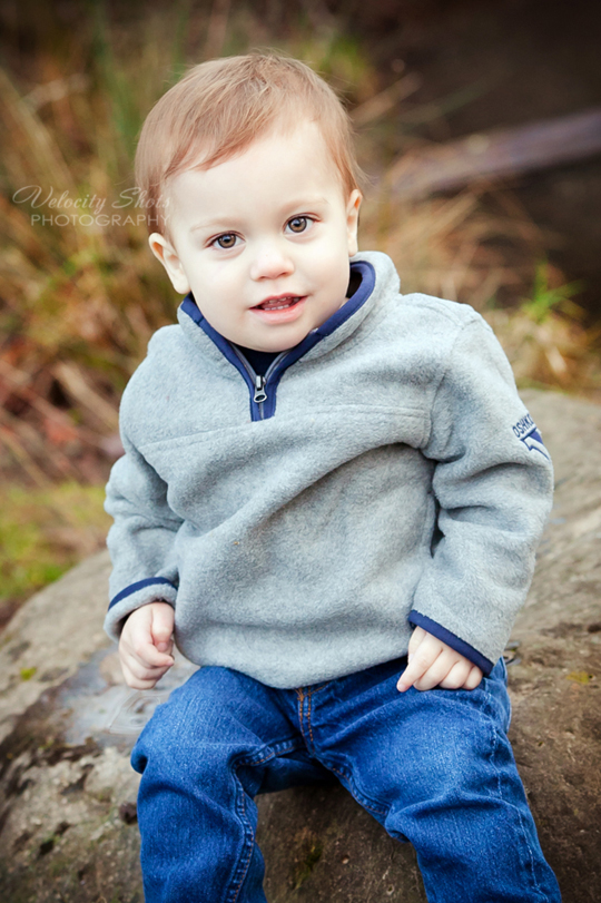 Toddler boy sitting on a rock